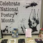 "table of books in front of a sign that says ""Celebrate National Poetry Month"""