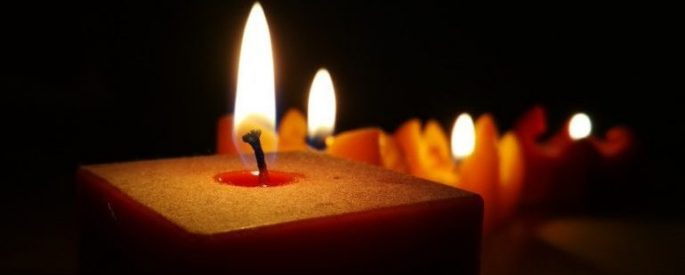 red lit candles against a black background
