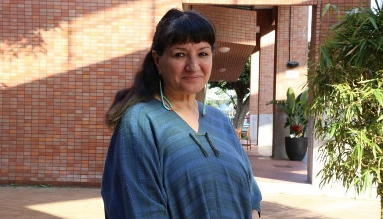 a photograph of Sandra Cisneros standing outdoors by a building