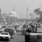 a US Marine tank patrols a Baghdad street, shares the road with civilian cars