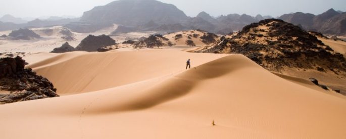 person walking up a vast sand dune