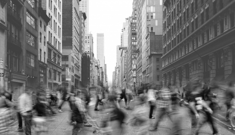 pedestrians blurred from motion walking across a street in New York City