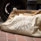 "bag with lettering that reads ""U.S. MAIL CITY COLLECTION"" on a brick sidewalk"