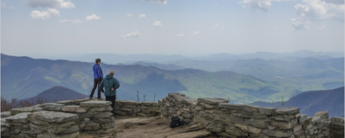 two people admire a vista of mountains