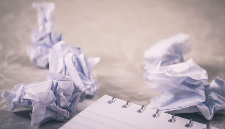 crumpled balls of paper around a corner of a notebook