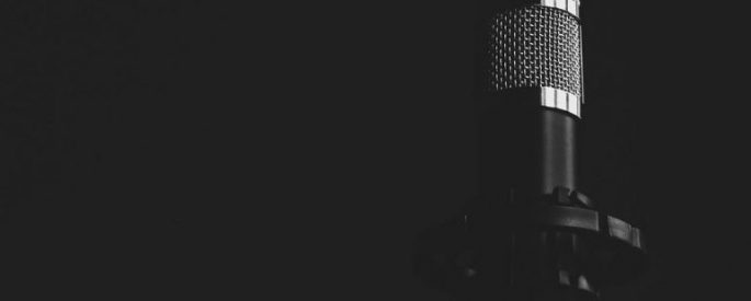microphone off to the side, against a black background