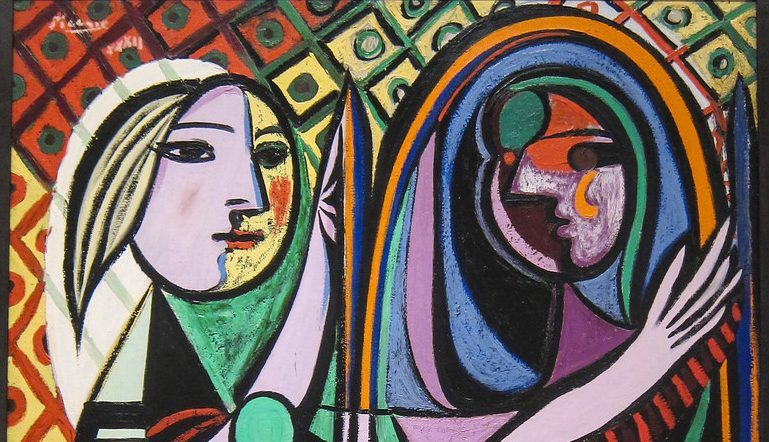 colorful, abstract Picasso painting of a woman in front of a mirror