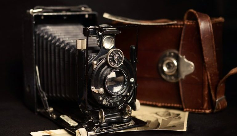 black view camera with brown case sitting on top of several vintage photographs