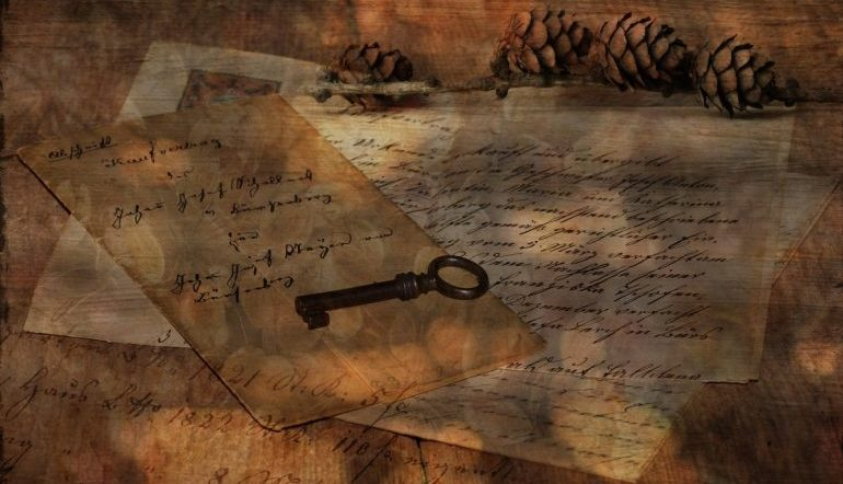 handwritten letters strewn on a surface with an old key on top and pine cones in a corner