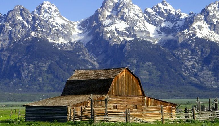 wooden barn in front of snow-capped mountains