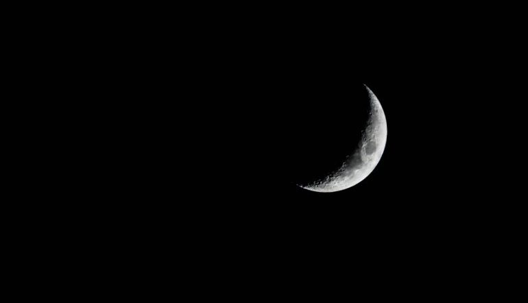black sky with a white crescent moon