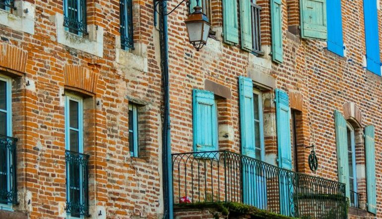 weathered brick facade with blue window shutters and a balcony