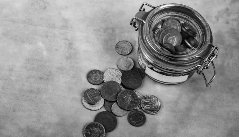 in black and white - glass tin of coins with coins scattered outside of it