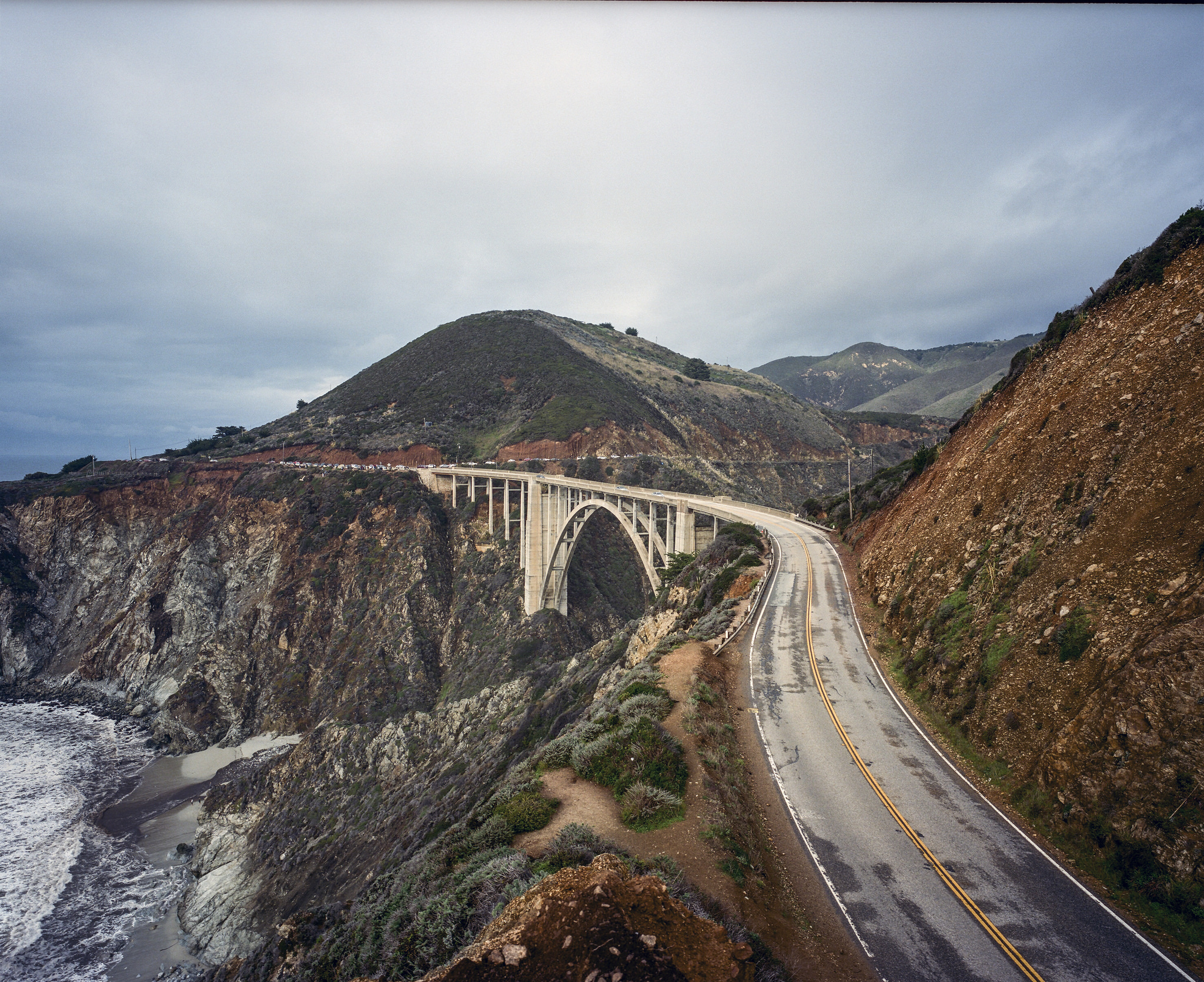Photograph of a highway bridge going between two mountains over the ocean