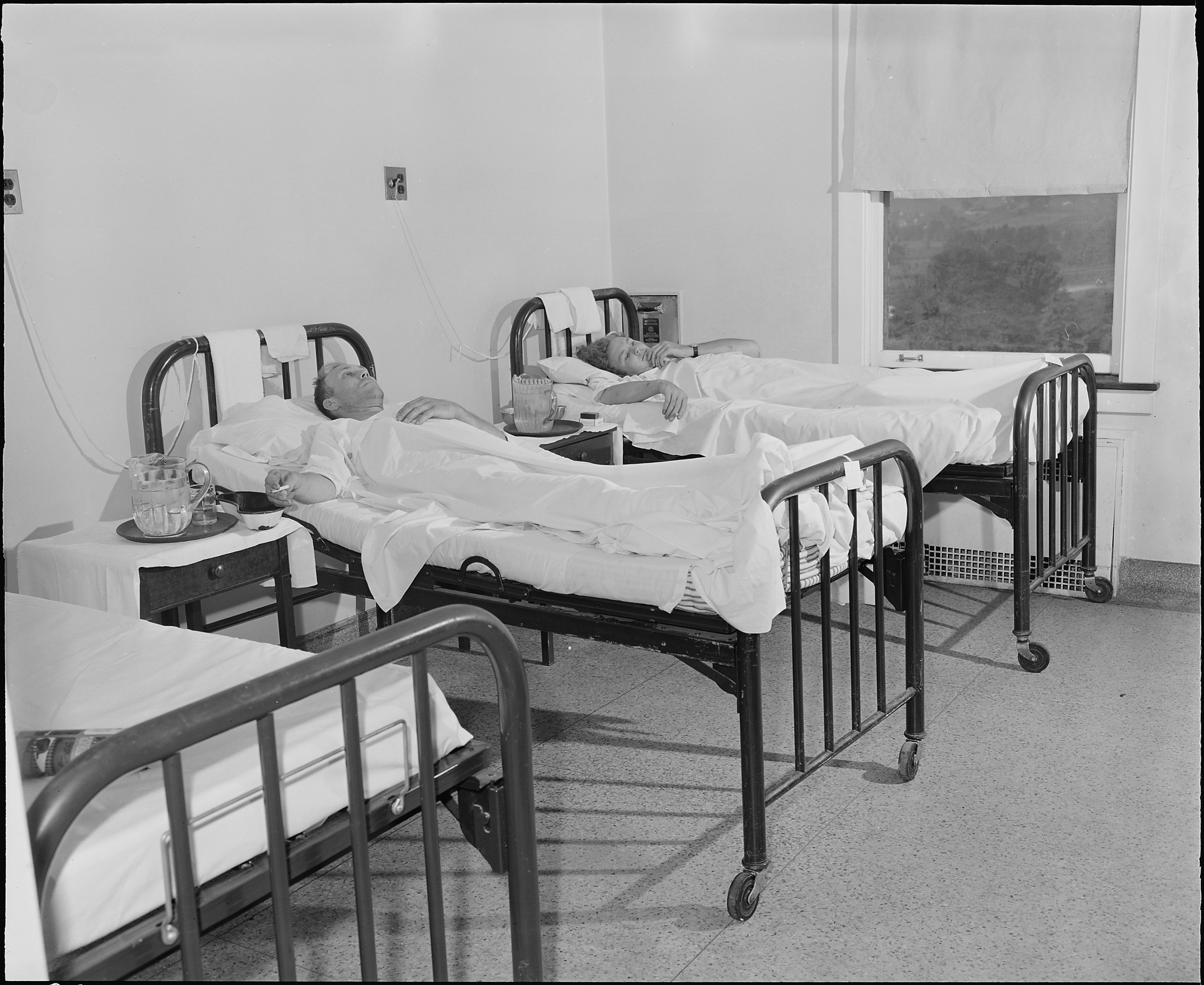 Black and white photo of two patients laying in hospital beds.