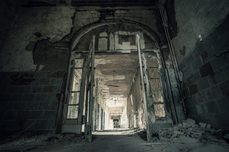 Image of an abandoned concrete building with a large open doorway with windowpanes.