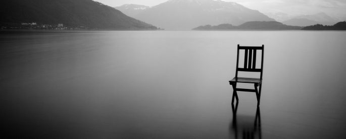 Black and white photograph of a chair out on a lake