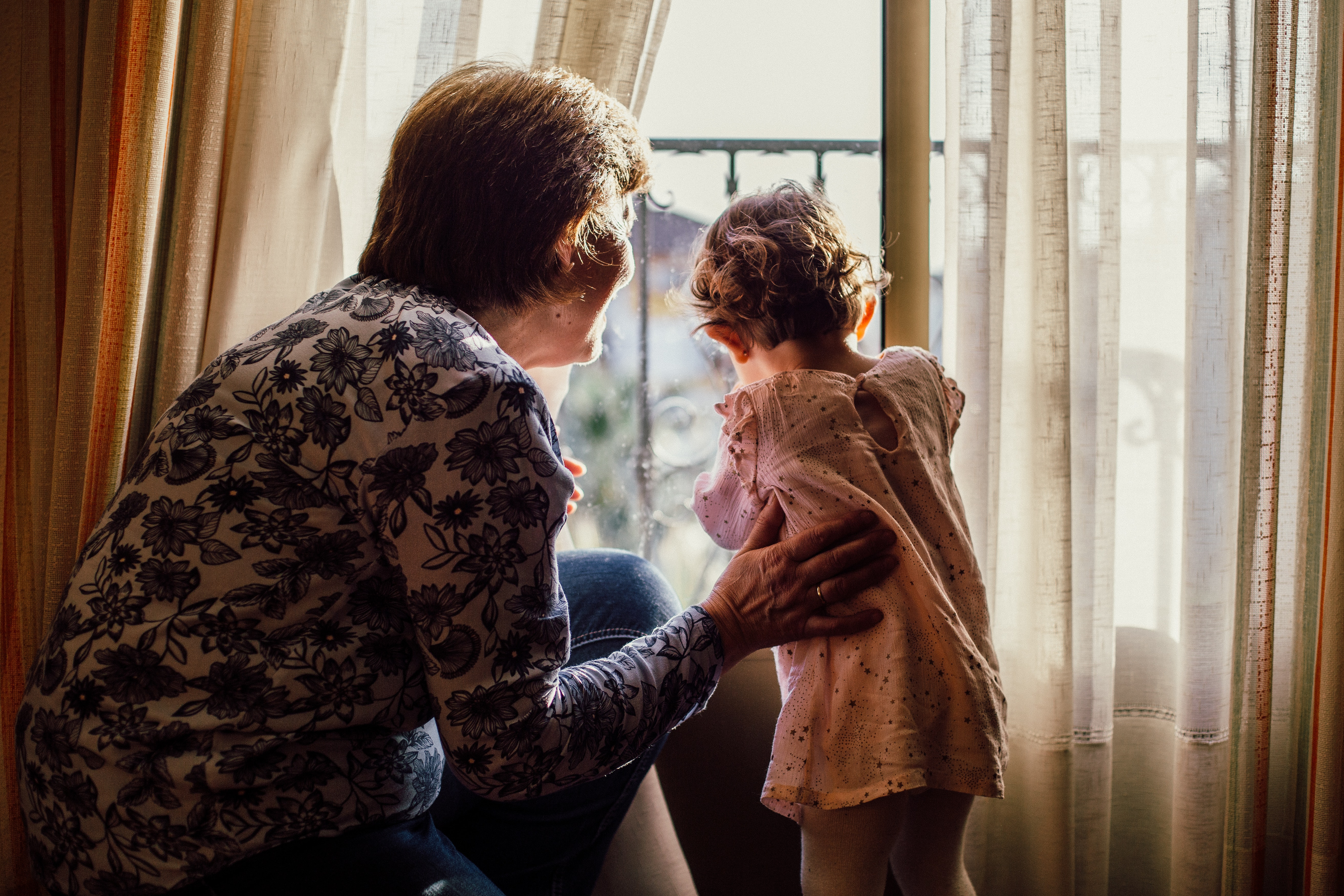 A grandmother looks out a window with her granddaughter