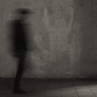 Black and white blurry photograph of a person standing against a cement wall