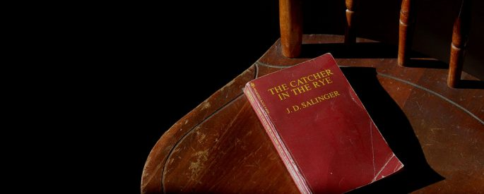 Photograph of an old copy of The Catcher in the Rye laying on an old chair