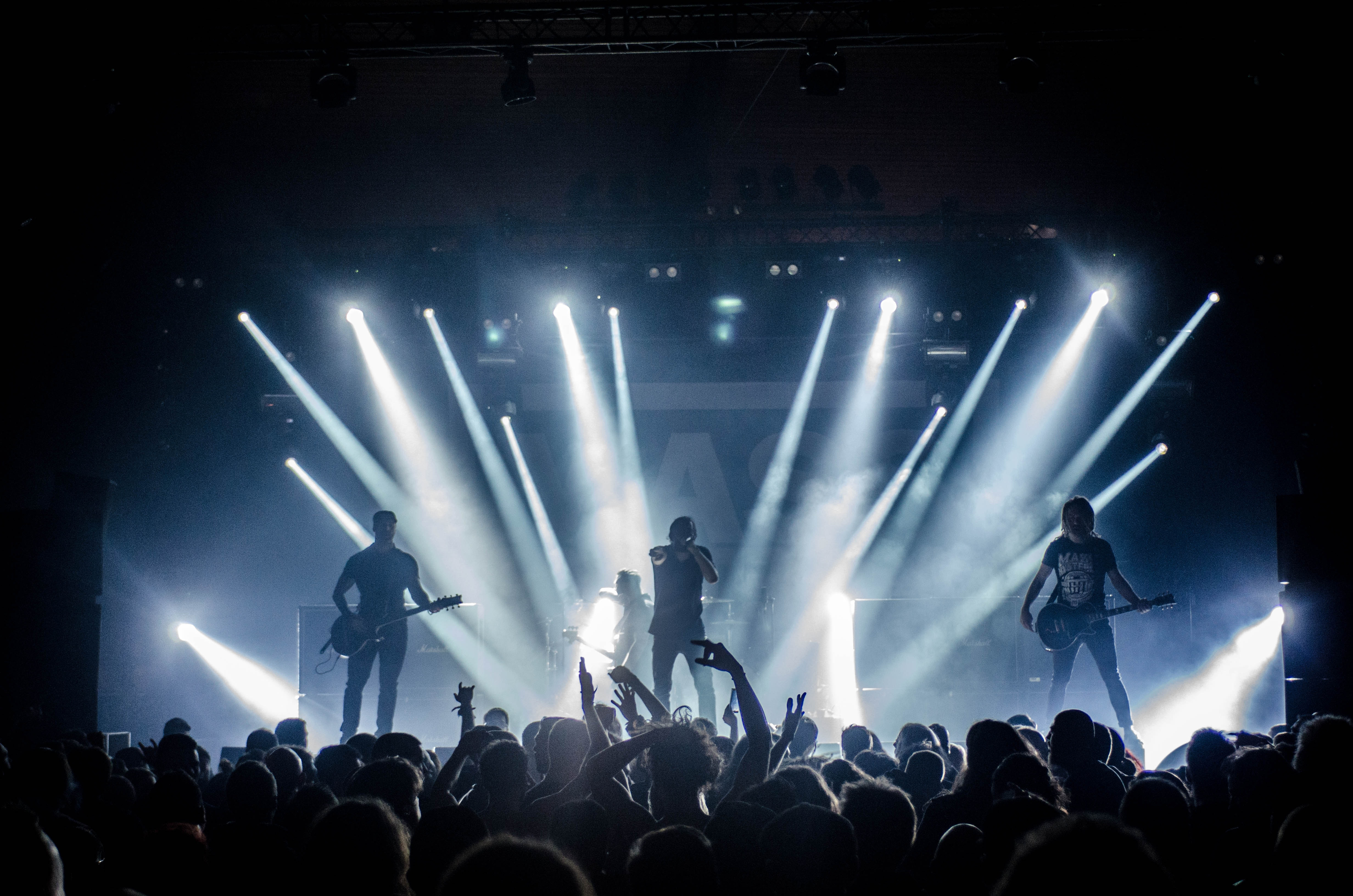 Photograph of a rock band performing on stage in front of a large audience.