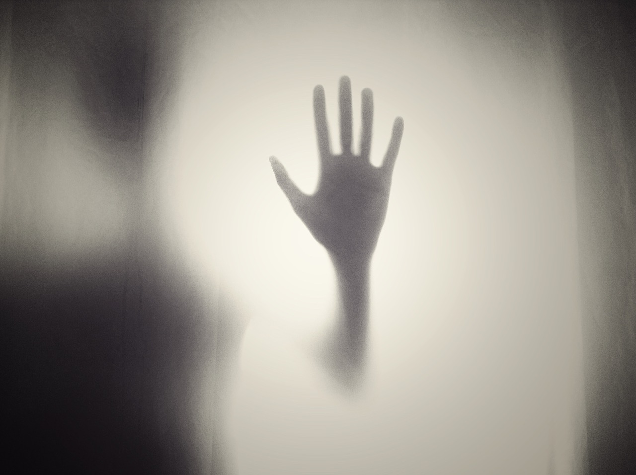 A hand is pressed against foggy glass.