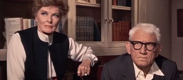 In a screengrab from Guess Who's Coming to Diner, Hepburn and Tracy are side by side staring at something off camera.