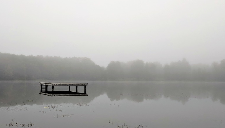 A lone dock sits in the middle of a grey, misty lake.