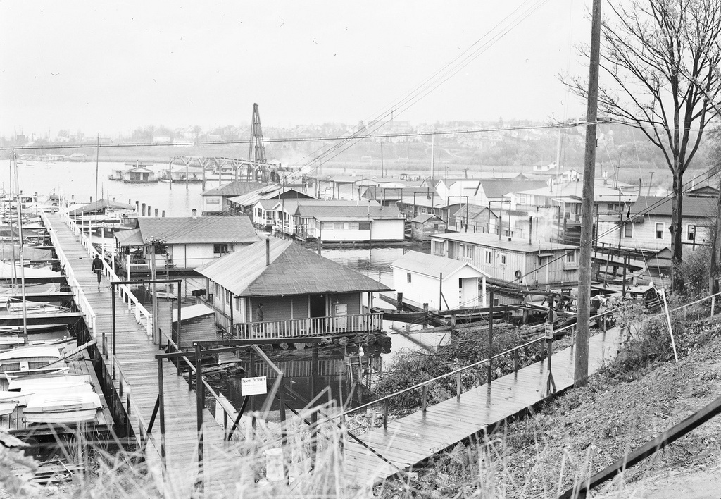 A black and white photo of old house boats on the water.