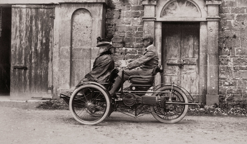 Violet Martin sitting in front of a man in an early car. Black and white.