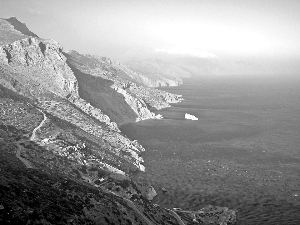 a black and white photograph of cliffs in Greece
