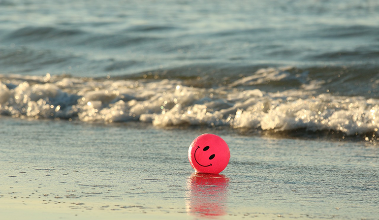 A beach ball with a smiley face painted on it sits on the beach