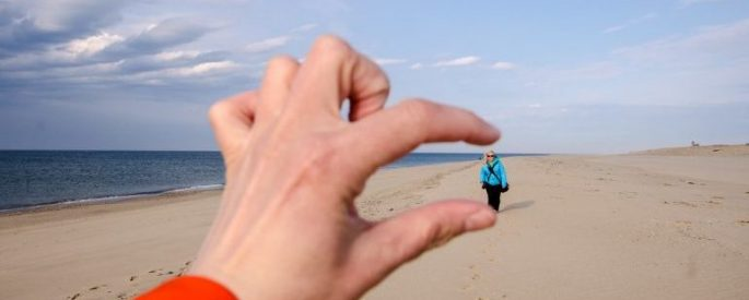 A photo of someone walking on a beach and the photographer's fingers seeming to crush the person walking