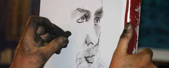 A hand sketching a charcoal portrait of a face