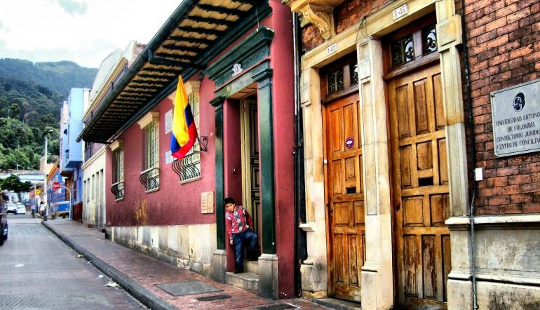 A street view of La Casa de Poesía Silva, two wooden doors with a small plaque next to them