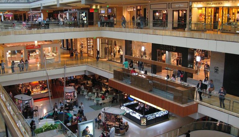 Open look at four levels of shopping mall with tables, stores, and lots of people