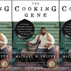 "Cover of ""The Cooking Gene"" by Michael Twitty, with a photo of the author sitting in front of a green building holding a bowl of food"