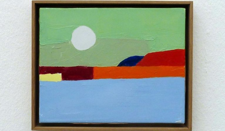 White wall with a framed painting centered. Painting shows a green sky, a white sun, red rocks, and blue water, all very abstract and color-blocked