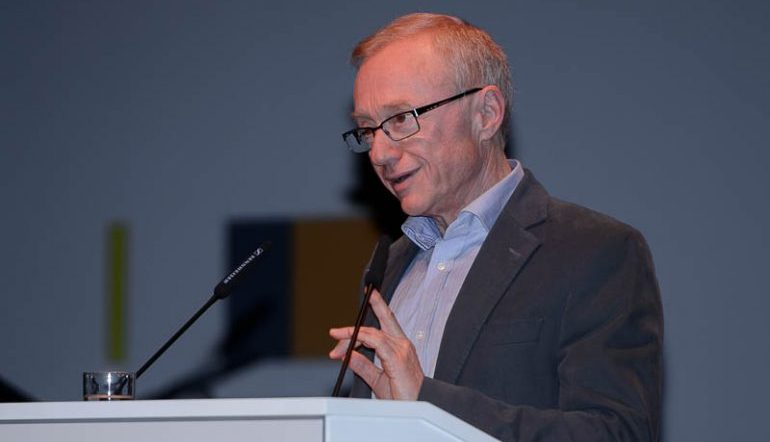 David Grossman standing behind a podium at a microphone speaking at an event