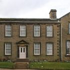 The front of the Bronte Parsonage Museum, a brick house with lots of windows