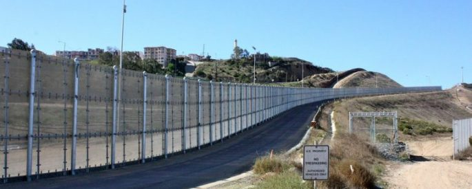 """Fenced border between US and Mexico with a sign that reads """"US Property, no trespassing"""""""