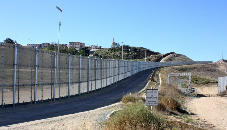 "Fenced border between US and Mexico with a sign that reads ""US Property, no trespassing"""
