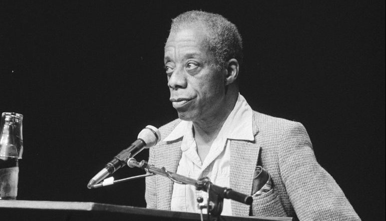Black and white photo of James Baldwin standing behind a podium speaking into a microphone