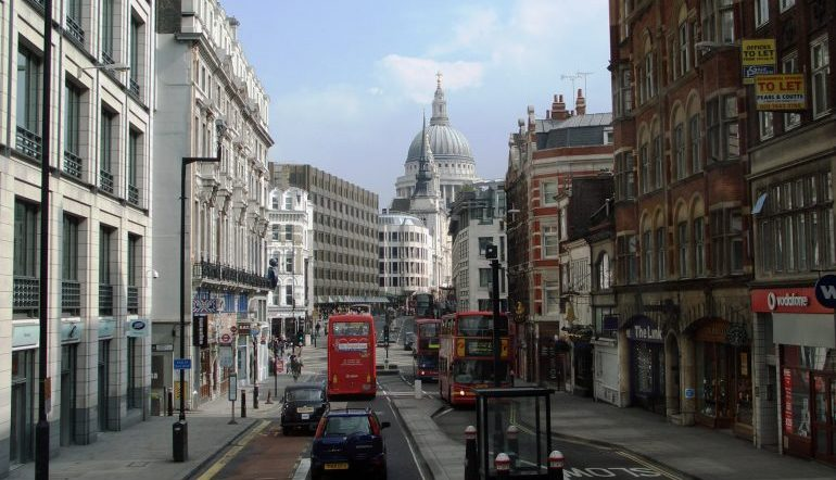 Street in London lined with both older and more modern buildings. A red doubledecker bus on one side and a large domed building in the skyline.