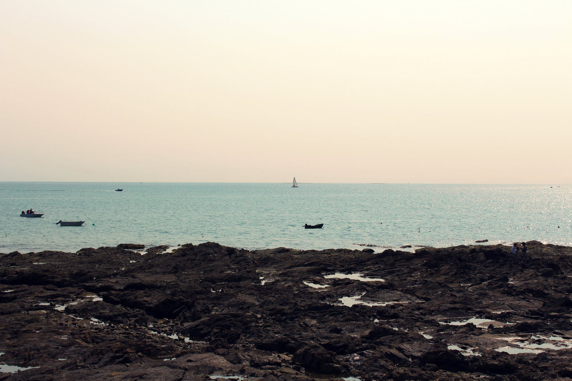 photograph of a rocky beach with sailboats in the distance