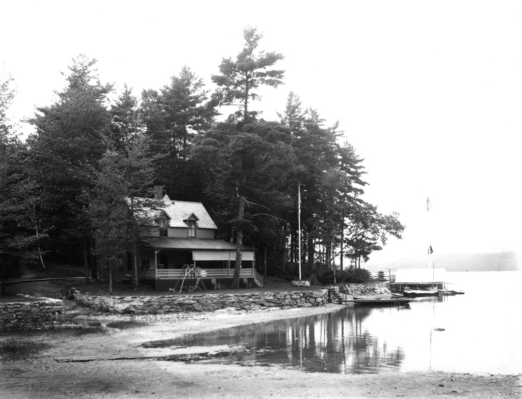 a black and white photograph of a house by a shallow river