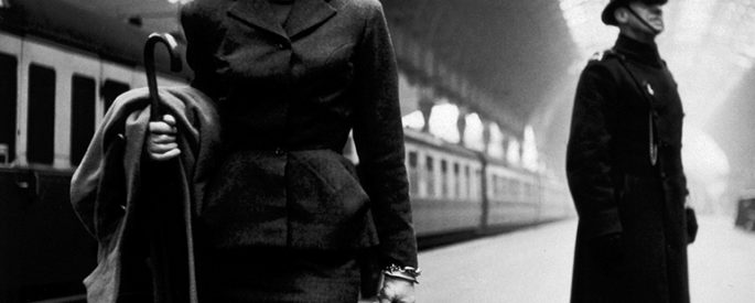 a woman in a nice suit waiting for a train station