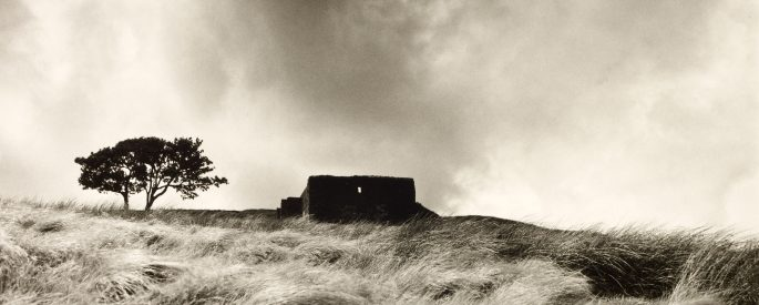 a black and white photograph of a ruined farmhouse seen from a distance