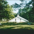 a photograph of a small white church in a wooded area