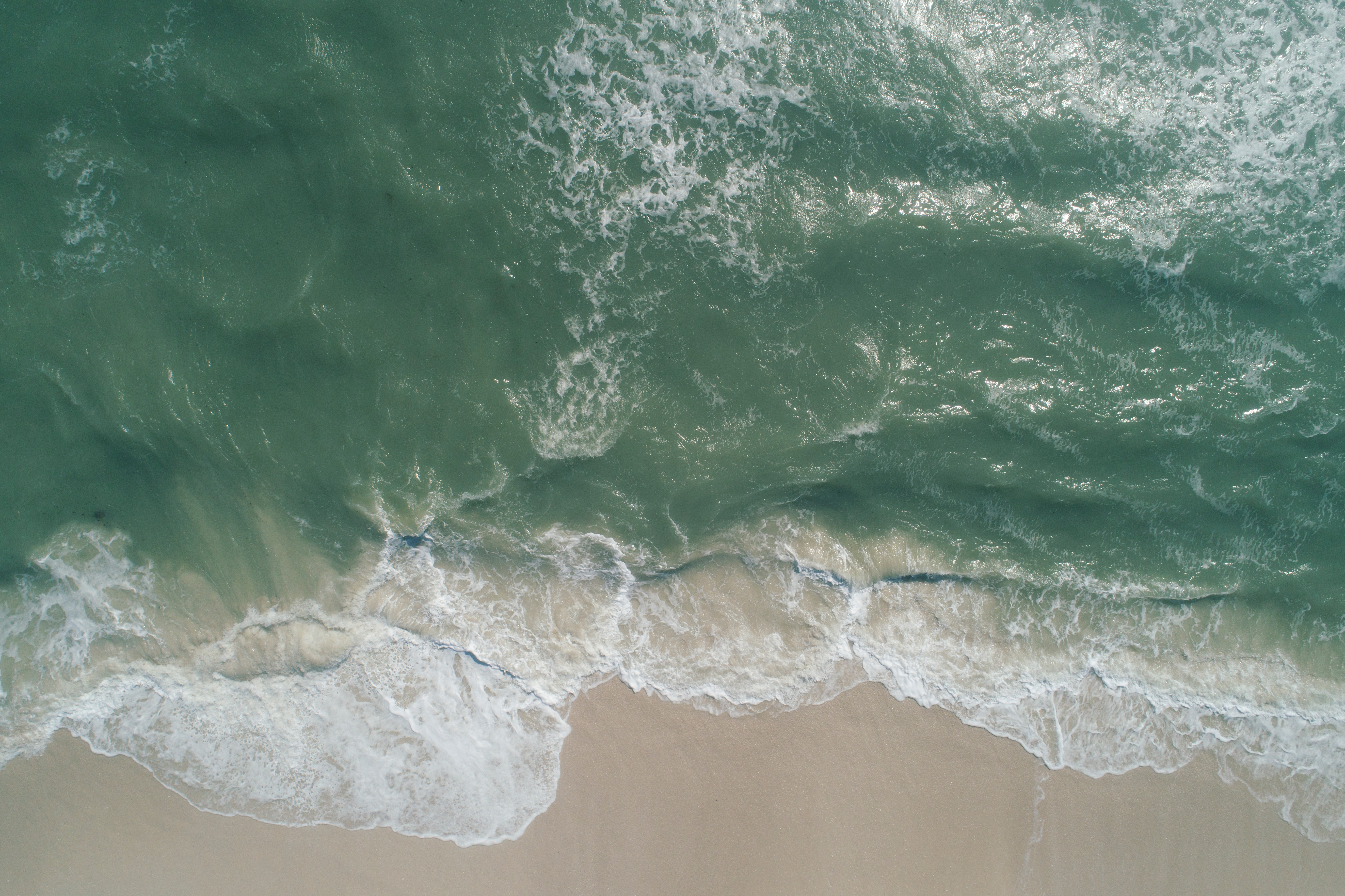 an aerial photograph of a green-ish ocean wave coming in to sand